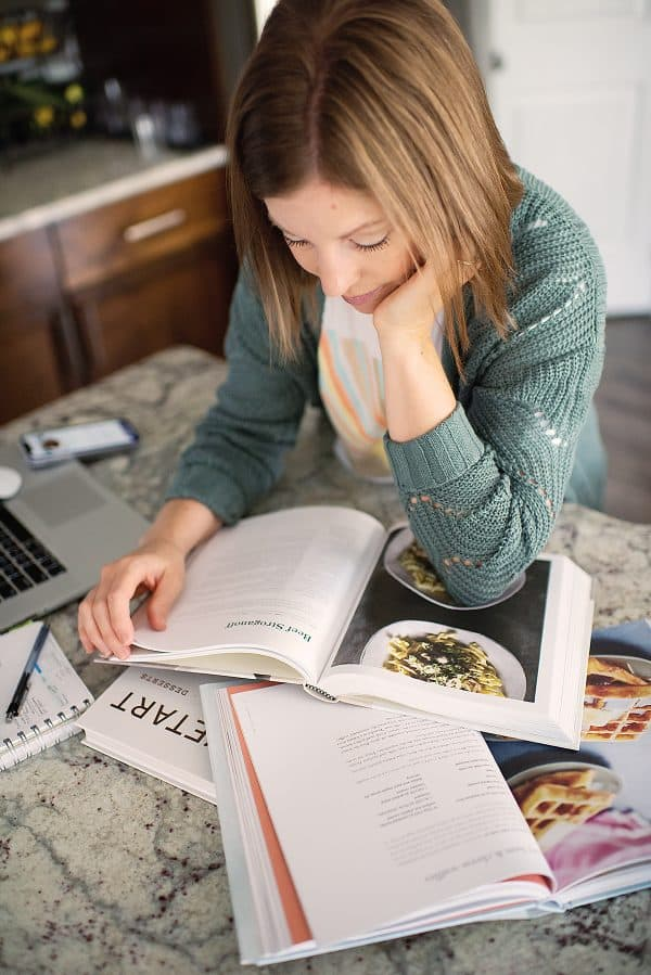 woman in green cardigan looking at cookbook