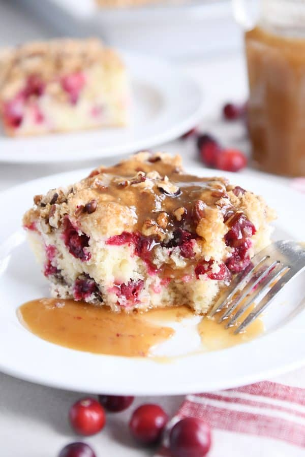 piece of cranberry coffee cake with warm vanilla sauce on white plate