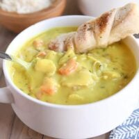 creamy chicken soup in white bowl with spoon and breadstick