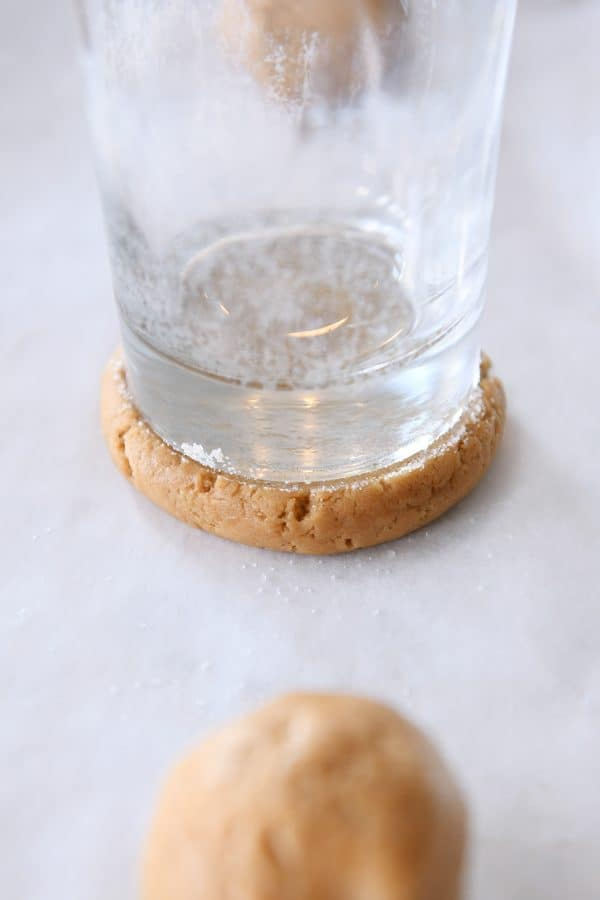 pressing ball of gingerbread sugar cookie dough with glass coated in sugar