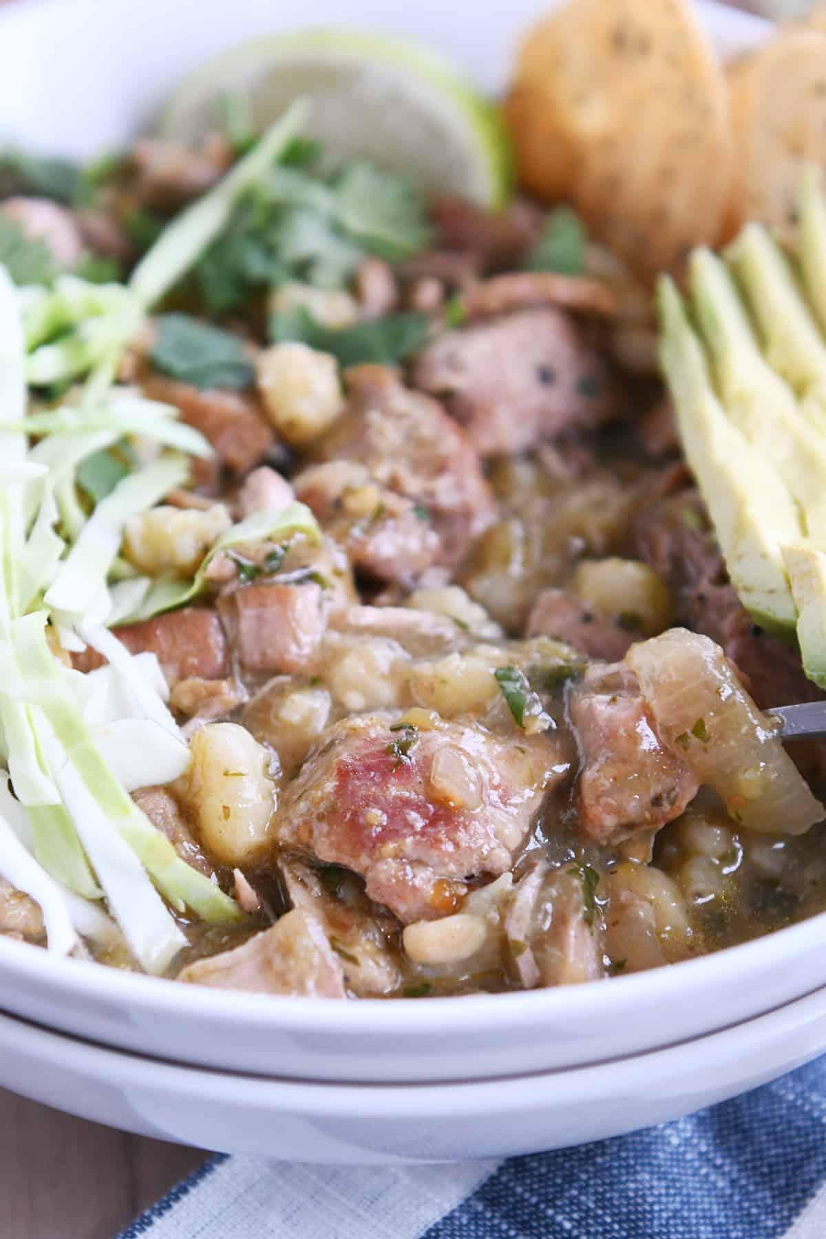 seasoned pork, hominy, broth, cabbage, avocado in white bowl