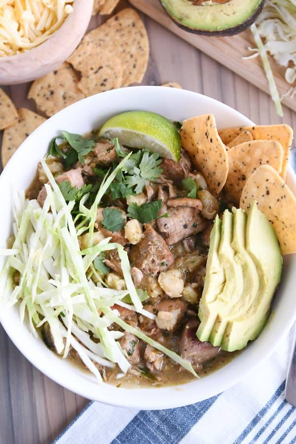 top down view of slow cooker posole in white bowl with shredded cabbage, sliced avocado, tortilla chips and lime wedge