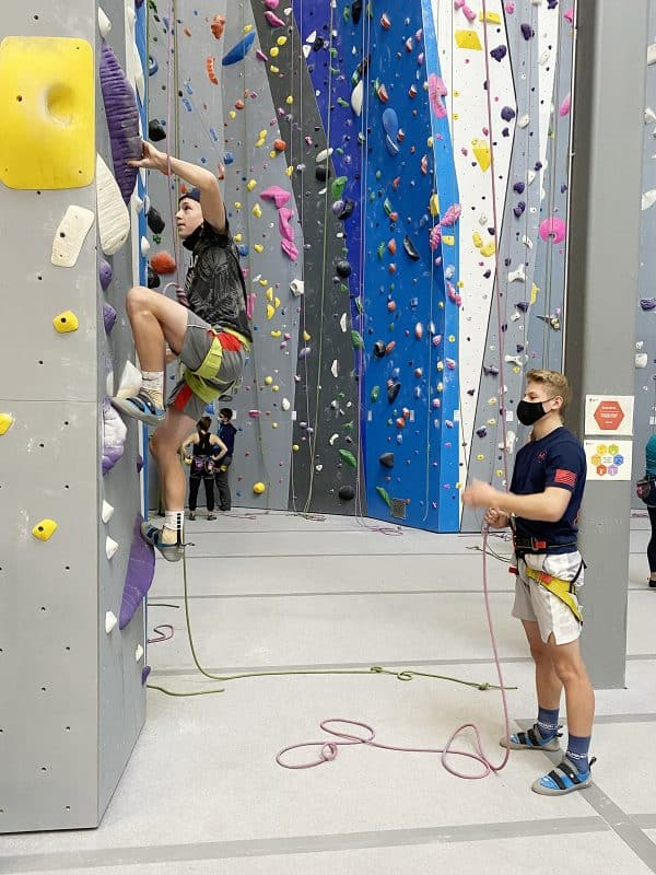 two teenage boys rock climbing