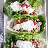 three greek lettuce wraps on white tray with cucumbers, tomatoes, with feta mint dressing