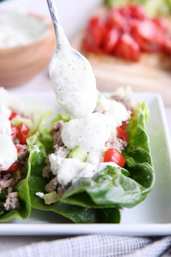 drizzling feta dressing on greek lettuce wraps on white tray