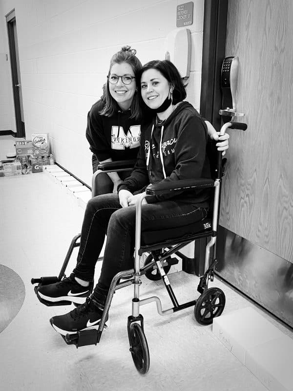 woman in wheelchair with friend standing by her side