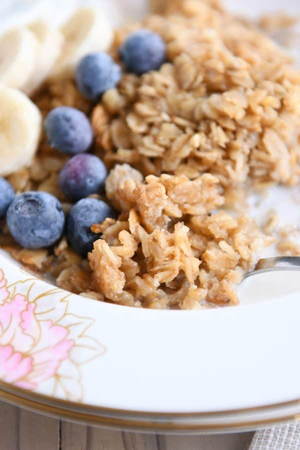 spoon underneath spoonful of baked oatmeal, blueberries and sliced bananas in floral bowl