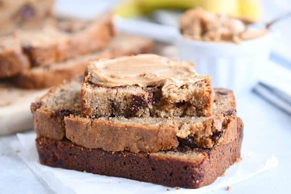 three peanut butter banana bread slices with peanut butter spread on top