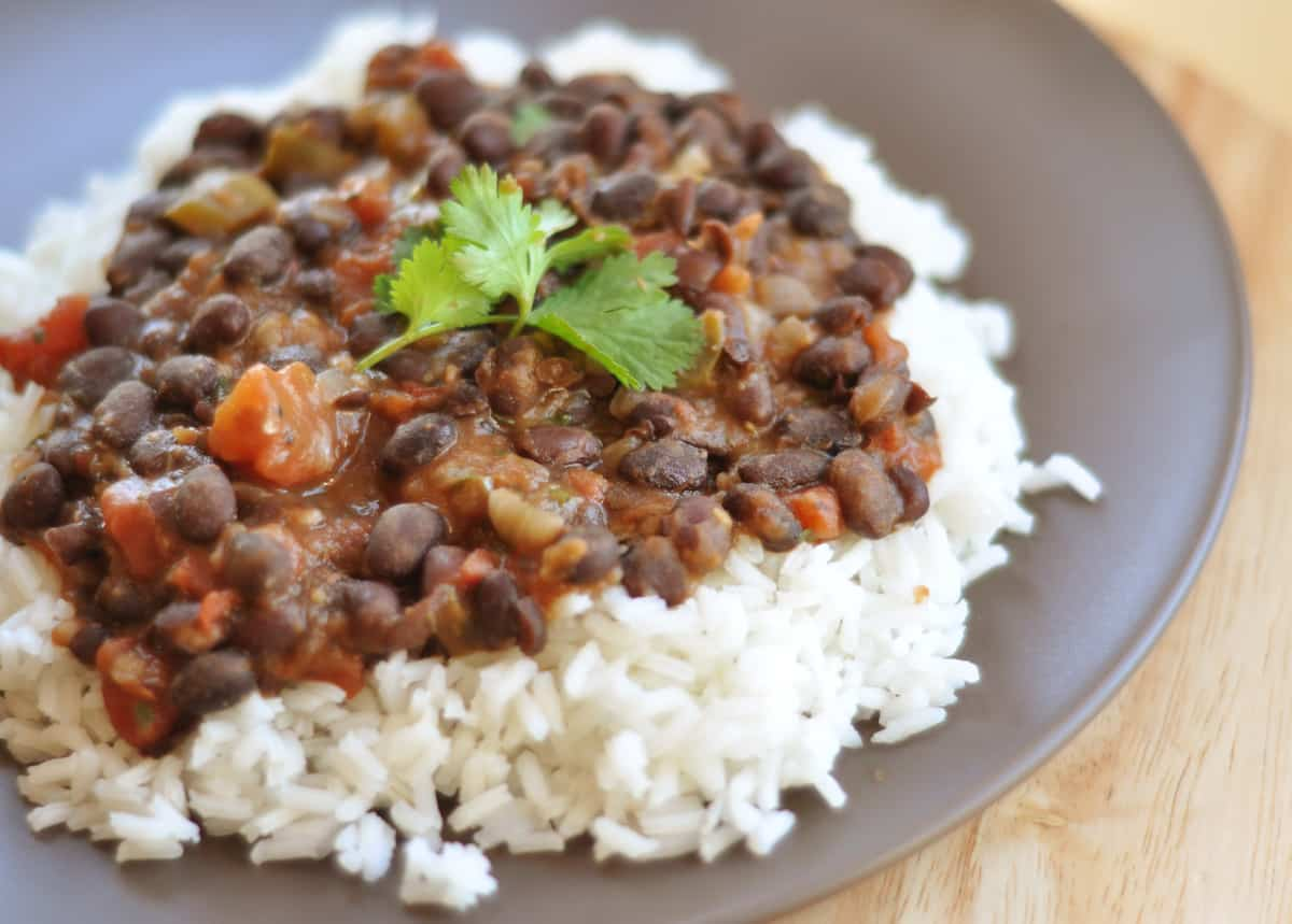 white rice topped with tomato and black bean mixture on a gray plate
