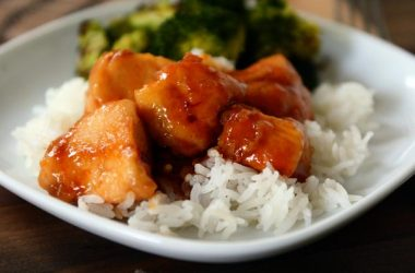 white plate with white rice and sticky glazed chicken cubes