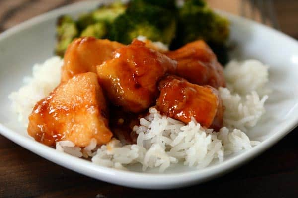 white rice and sticky bourbon chicken with a side of broccoli on a white plate
