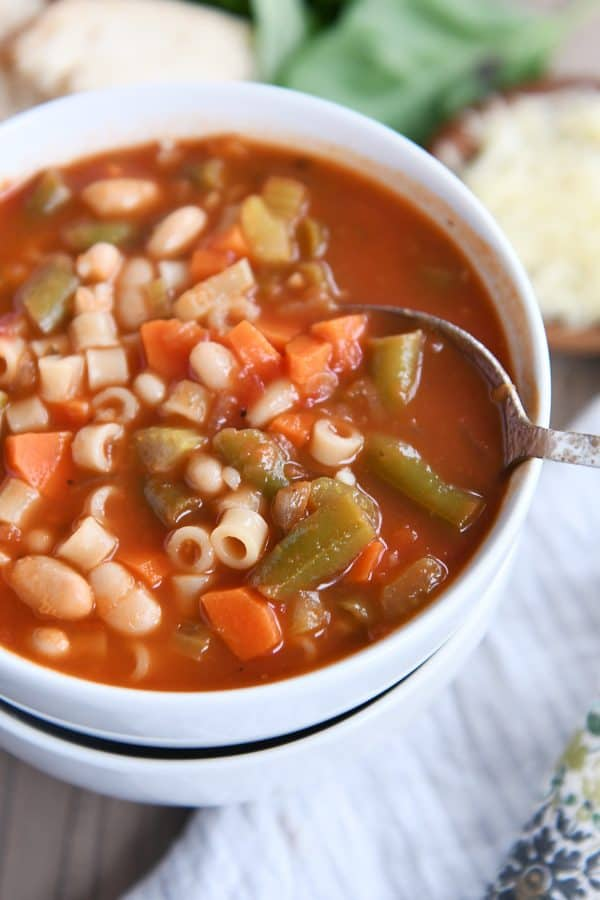 spoon in bowl of classic minestrone soup in two stacked white bowls