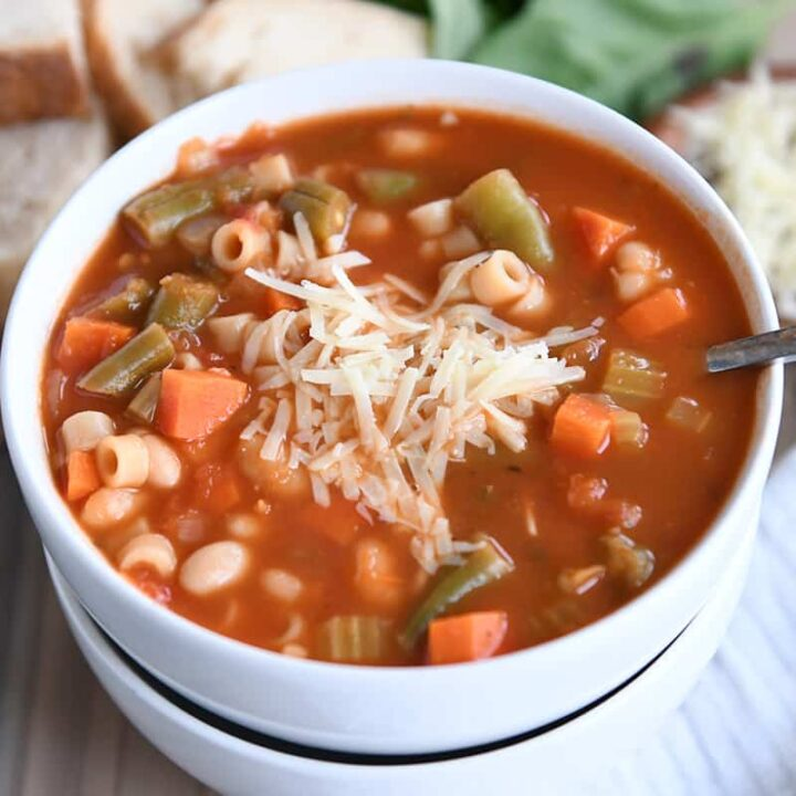 minestrone soup in two stacked white bowls with parmesan cheese