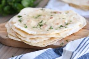 stack of easy yogurt flatbread on wood cutting board sprinkled with parsley