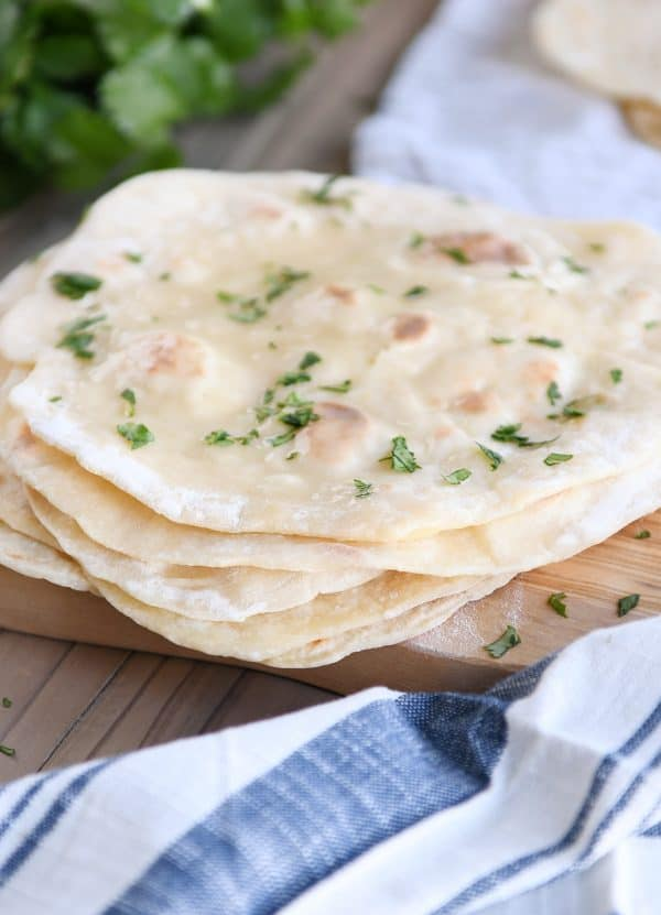 stack of cooked yogurt flatbreads on wood cutting board