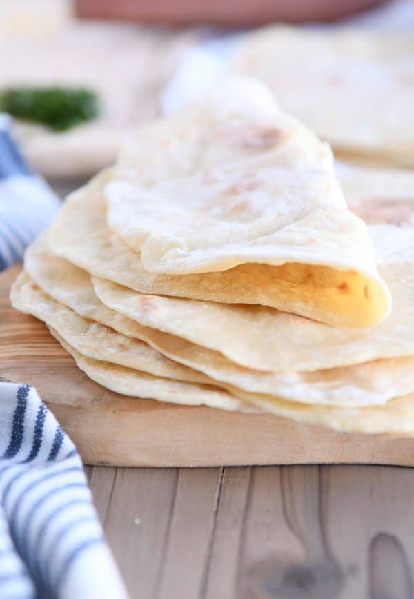 folded piece of yogurt flatbread on stack of four flatbreads