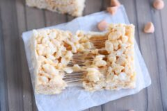 butterscotch rice krispie pulled in half on white parchment paper