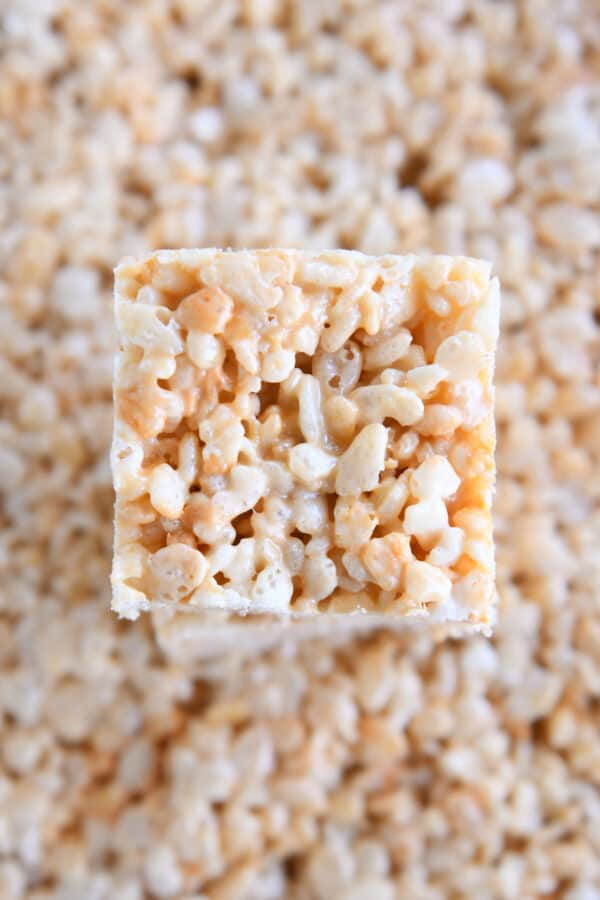 square of butterscotch rice krispie treat on top of 9X13-inch pan of treats