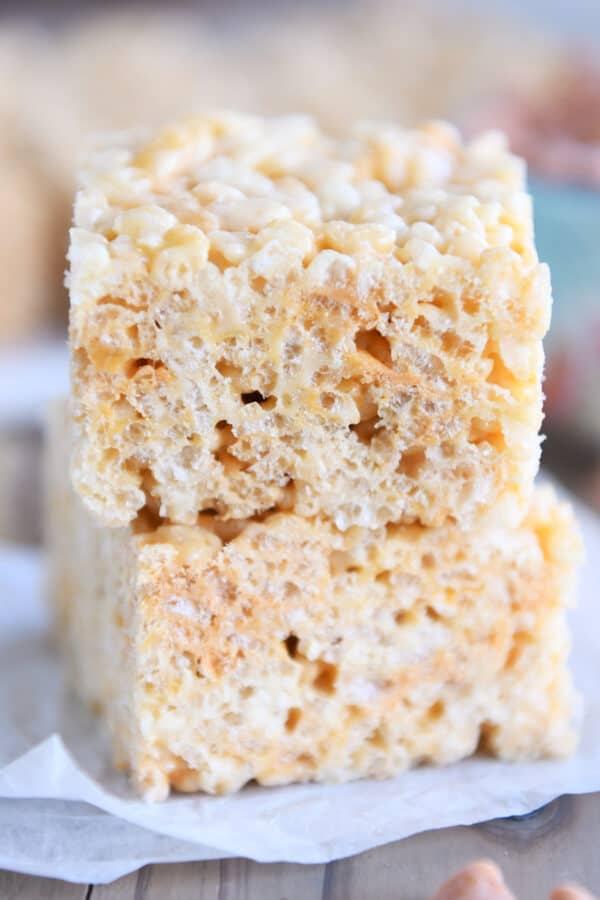 two rice krispie treats stacked on piece of white parchment paper