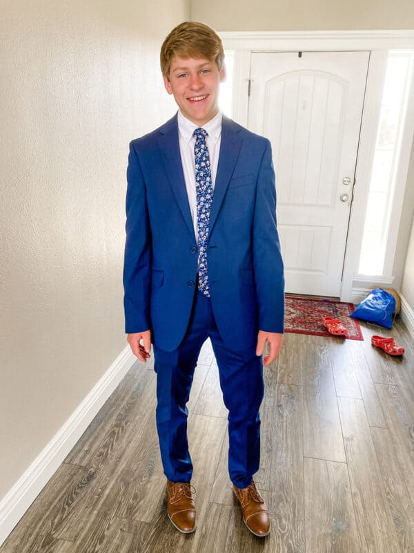 teenager in blue suit next to wall