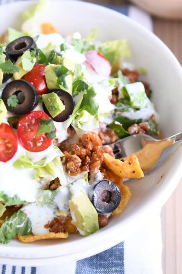 white bowl filled with corn chips, taco meat and taco toppings