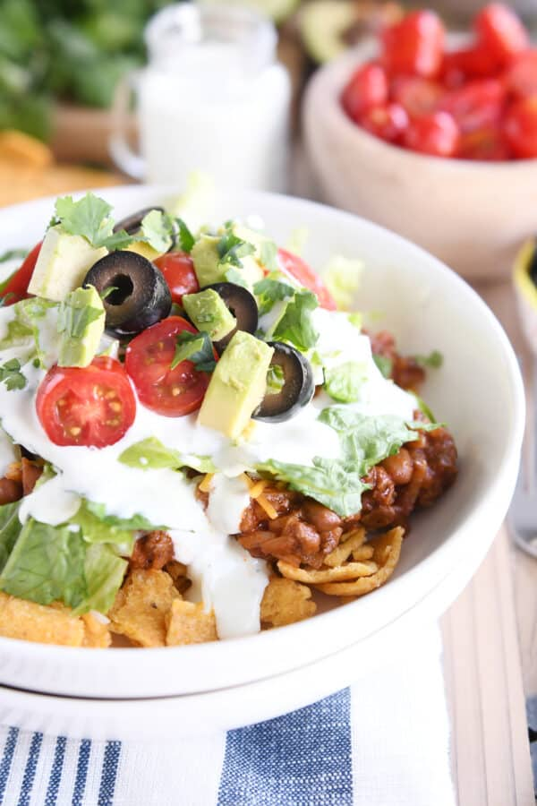 floating taco bowls in white bowl with lettuce, tomatoes and olives