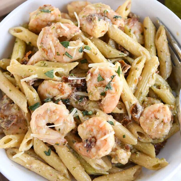 pasta with shrimp, parmesan and sun-dried tomatoes in white bowl with fork