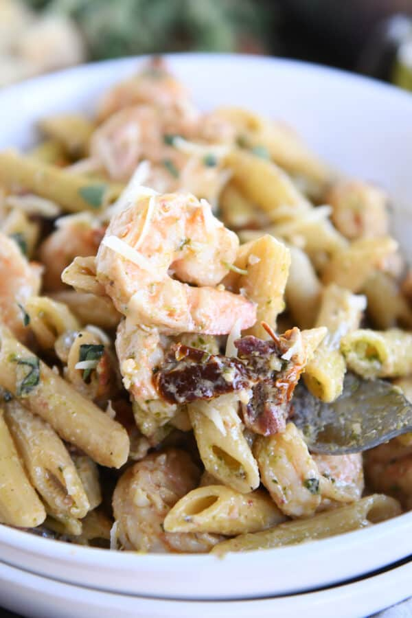 shrimp, pasta, sun-dried tomatoes in white bowl with fork