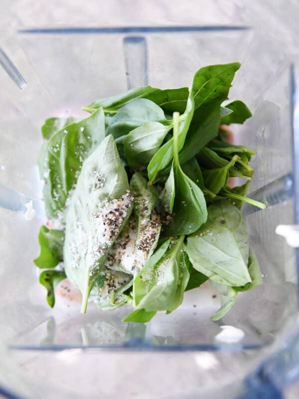blender with fresh basil leaves, salt and pepper