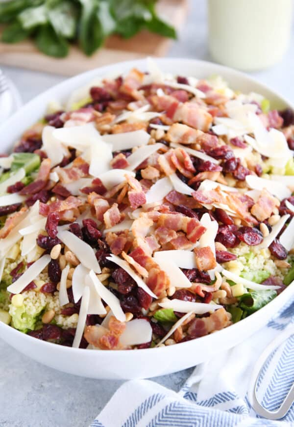 white serving bowl with romaine lettuce, bacon, parmesan, craisins, and pine nuts