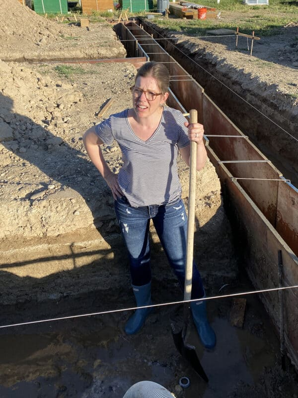 woman standing in mud filled trench with shovel