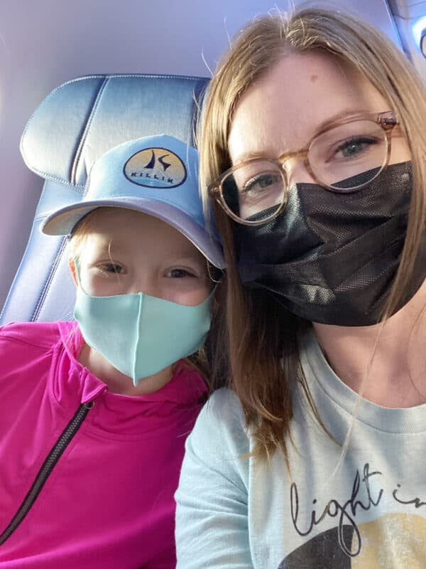 mom and daughter on plane with masks