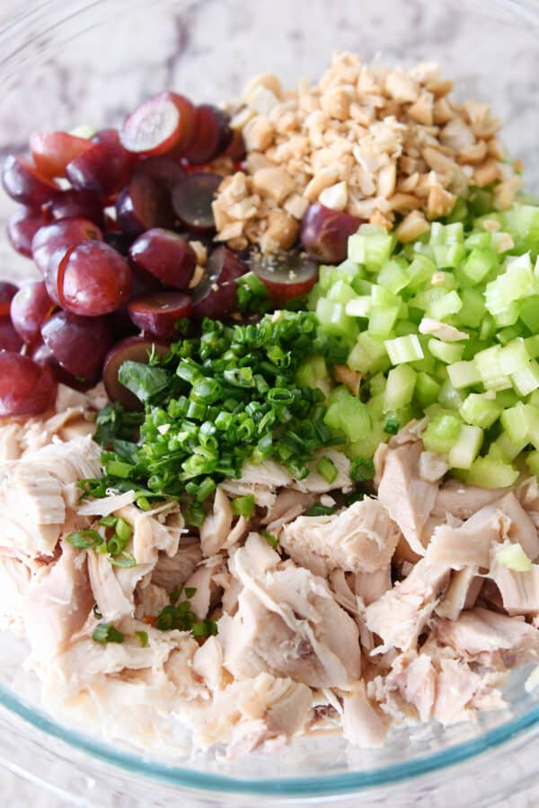 shredded chicken, green onions, celery, grapes and nuts in glass bowl