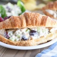 chicken salad on whole croissant on white plate