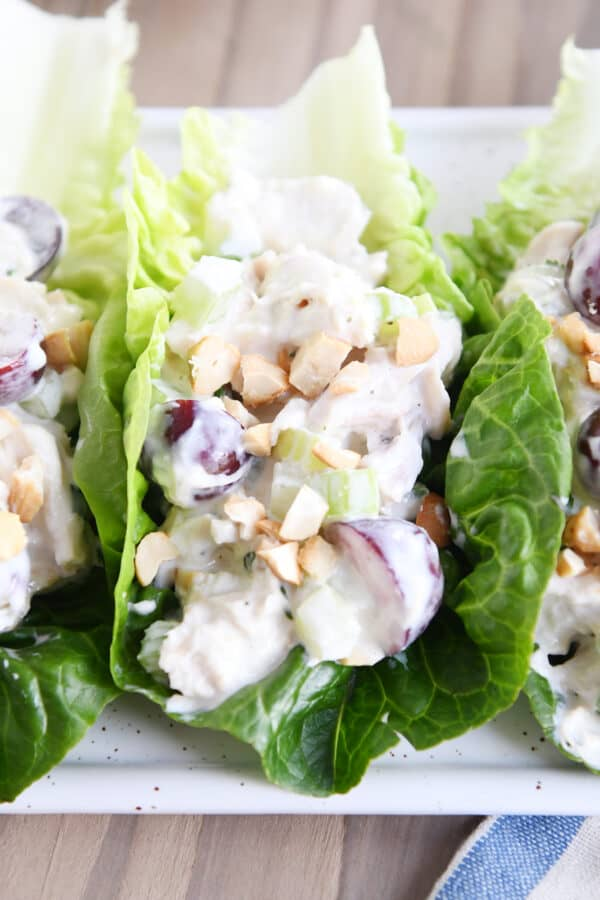 chicken salad recipe on bed of lettuce leaves on white platter