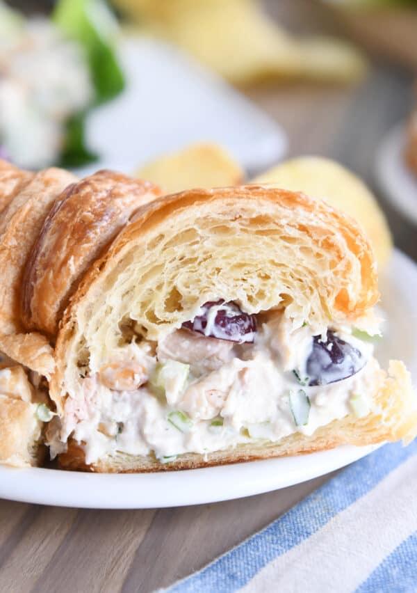 chicken salad sandwich on croissant cut in half on white plate