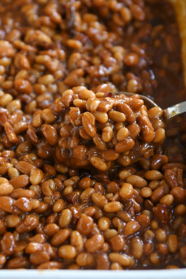 scooping spoon in pan of saucy baked beans