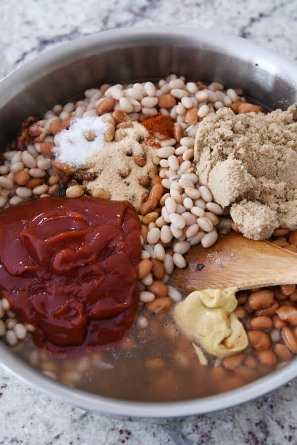 white beans, brown sugar, ketchup, broth, dijon mustard in shallow pan with wooden spoon