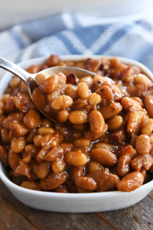 spoon scooping out spoonful of saucy baked beans in white square dish