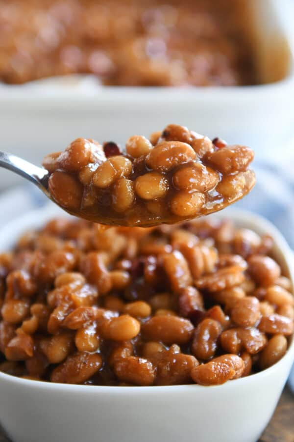 spoonful of saucy baked beans over white square dish