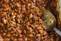 slotted spoon in dish of saucy baked beans