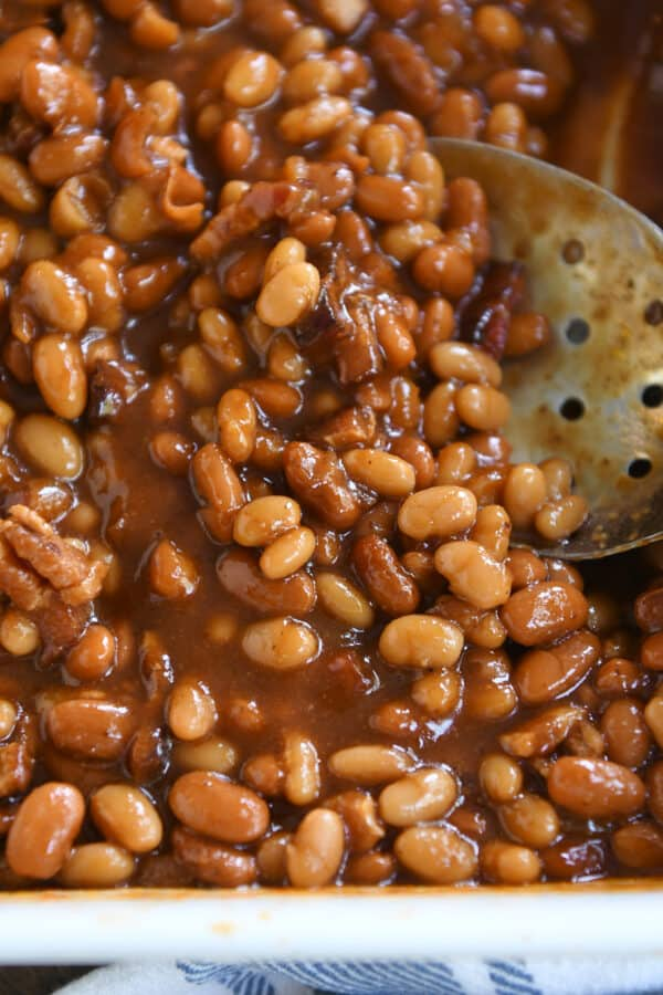 slotted serving spoon scooping baked beans in white dish