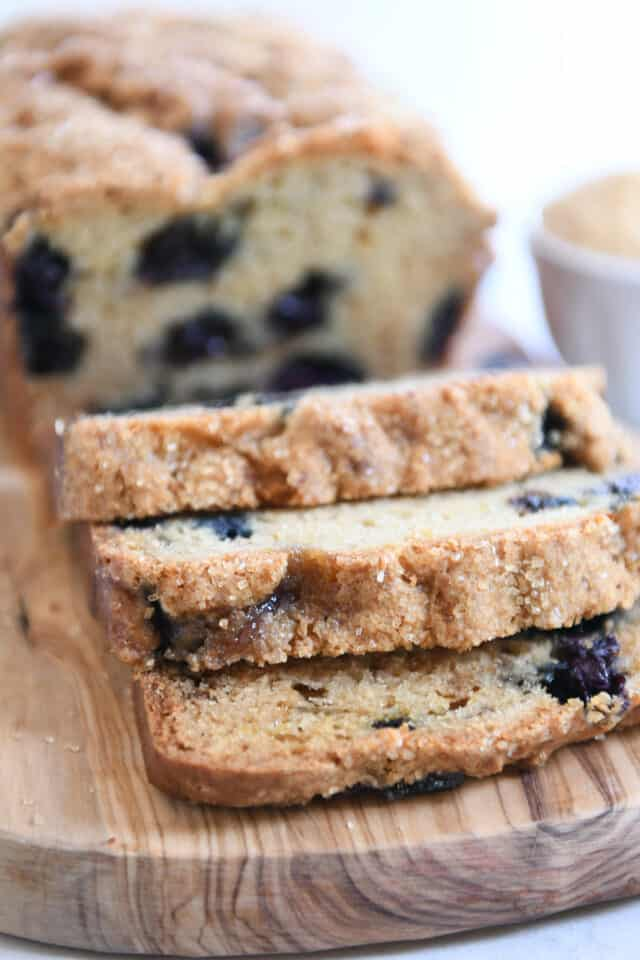 three slices of blueberry muffin bread cut from the loaf on wood cutting board