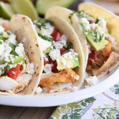 three fish tacos in corn tortillas on white platter