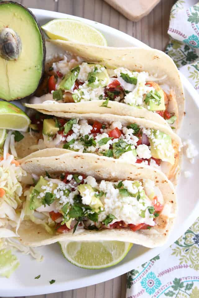 three fish tacos on white platter with avocado and lime wedges