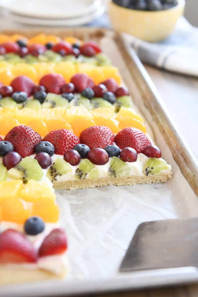 sheet pan of fruit pizza with a serving taken out with metal spatula