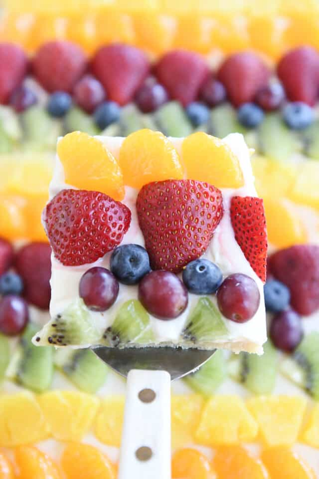square of fruit pizza with mandarin oranges, strawberries, blueberries, red grapes and kiwi above sheet pan fruit pizza
