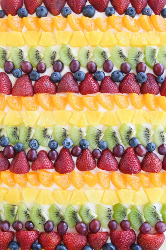 rows of kiwi, red grapes, blueberries, strawberries, mandarin oranges and pineapple on fruit pizza