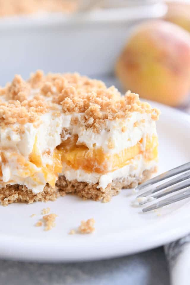 square of peaches and cream dessert on white plate with fork