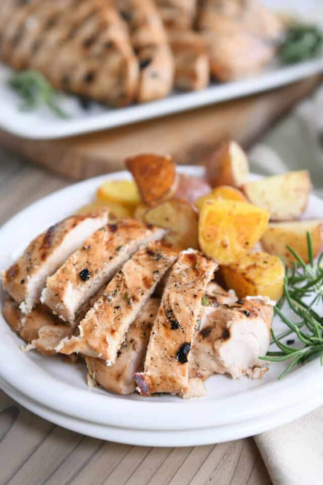 white plate with strips of grilled rosemary ranch chicken, fresh rosemary sprig and roasted potatoes